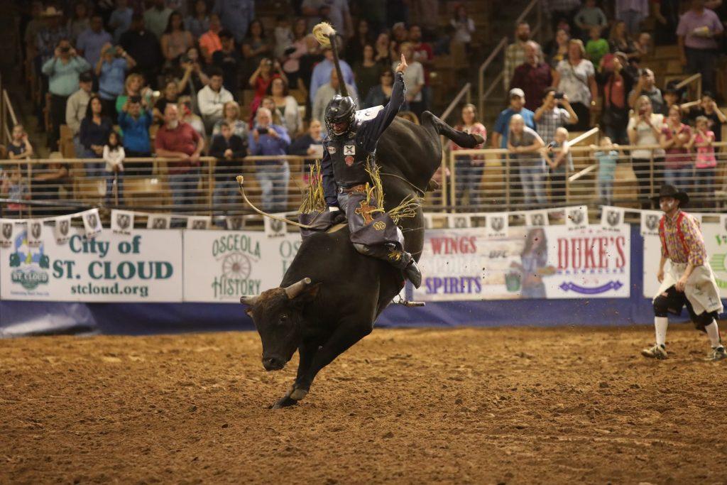 bull rider riding a bull at a rodeo